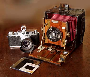 A Leica 2F of 1956 and an Edwardian 'Sanderson' 1/4 plate hand & stand. A 35mm slide and a Lantern Slide